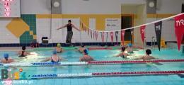 Na zdjęciu widoczne są uczestniki zajęć aqua aerobic podczas rozgrzewki.