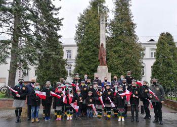 Na zdjęciu znajdują się przedstawiciele władz samorządnych oraz powiatu,  harcerze oraz zuchy buskiego hufca na tle pomnika Tadeusza Kościuszki w Busku-Zdroju.