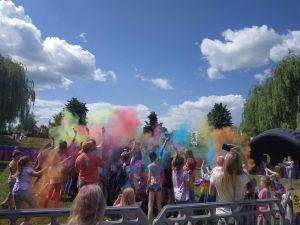 Na zdjęciu widoczni są uczestnicy Holi Święta Kolorów podczas wyrzutu kolorowych proszków holi.
