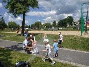 Na zdjęciu widoczne są dzieci bawiące się wśród dmuchanych baniek dymnych.