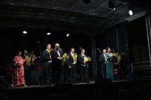 Zdjęcie przedstawia przemawiającą dyrektor BSCK , organizatora festiwalu oraz tenorów występujących podczas Gali Festiwalowej  XXVI Międzynarodowego Festiwalu im. Krystyny Jamroz.