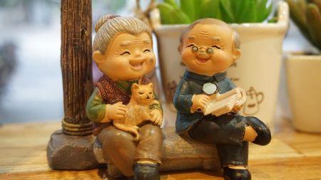 Zdjęcie przedstawia figurkę uśmiechniętej babci trzymającej na kolanach kota oraz siedzącego obok niej uśmiechniętego dziadka trzymającego lupę i książkę.