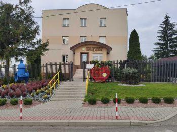 Zdjęcie przedstawia metalowy pojemnik w kształcie serca na nakrętki na tle budynku MPGK w Busku-Zdroju