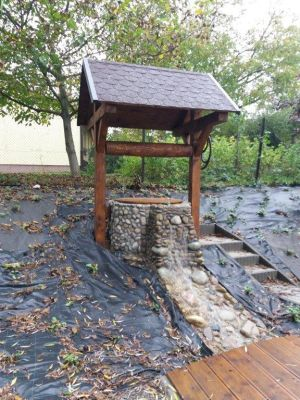 """Zdjęcie przedstawia kamienną studnię znajdującą się na terenie Stawu Niemieckiego oraz małą drewnianą kładkę (koryto łączące staw z tzw. """"studnią–fontanną""""). Fot. K. Chmura"""