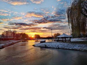Zdjęcie przedstawia zimowy  zachód słońca nad Stawem Niemieckim w tle którego widać domek dla łabędzi, drewnianą budkę lęgową dla kaczek oraz drewnianą platformę lęgową dla łabędzi. Fot. K. Chmura